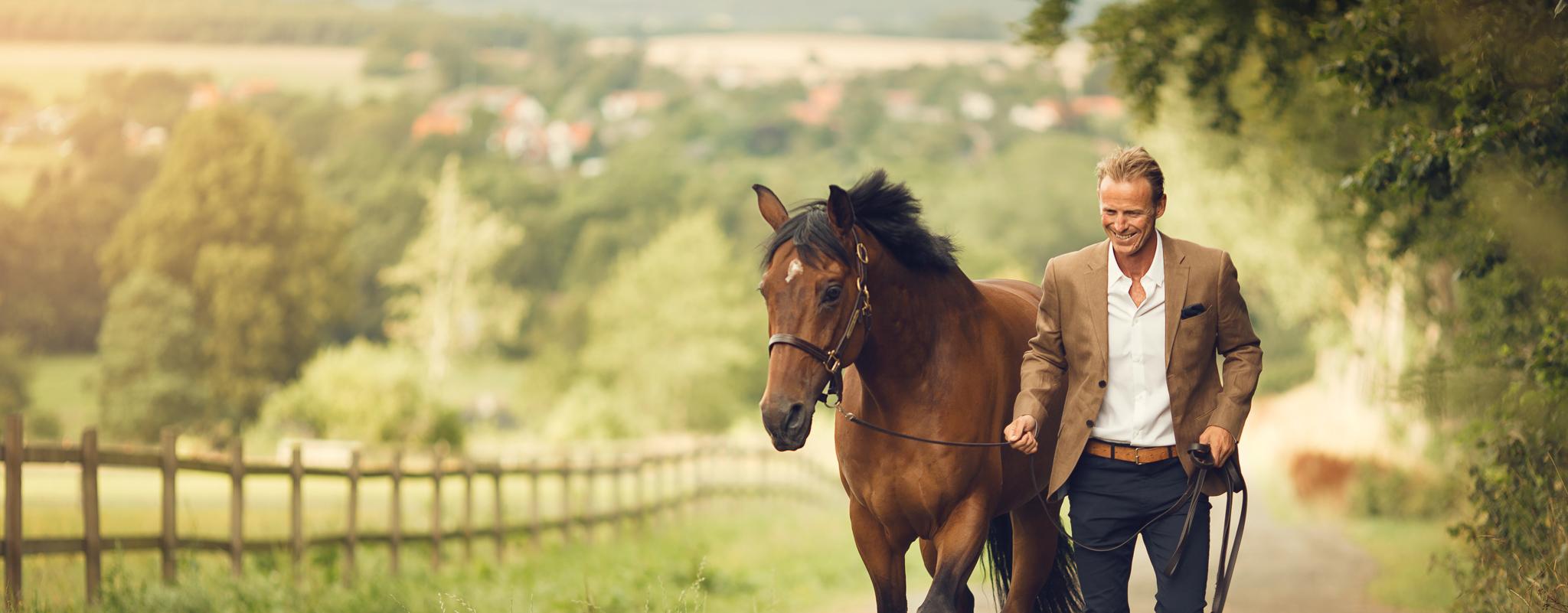 Peder och en häst fotograferas med landskapet som bakgrund