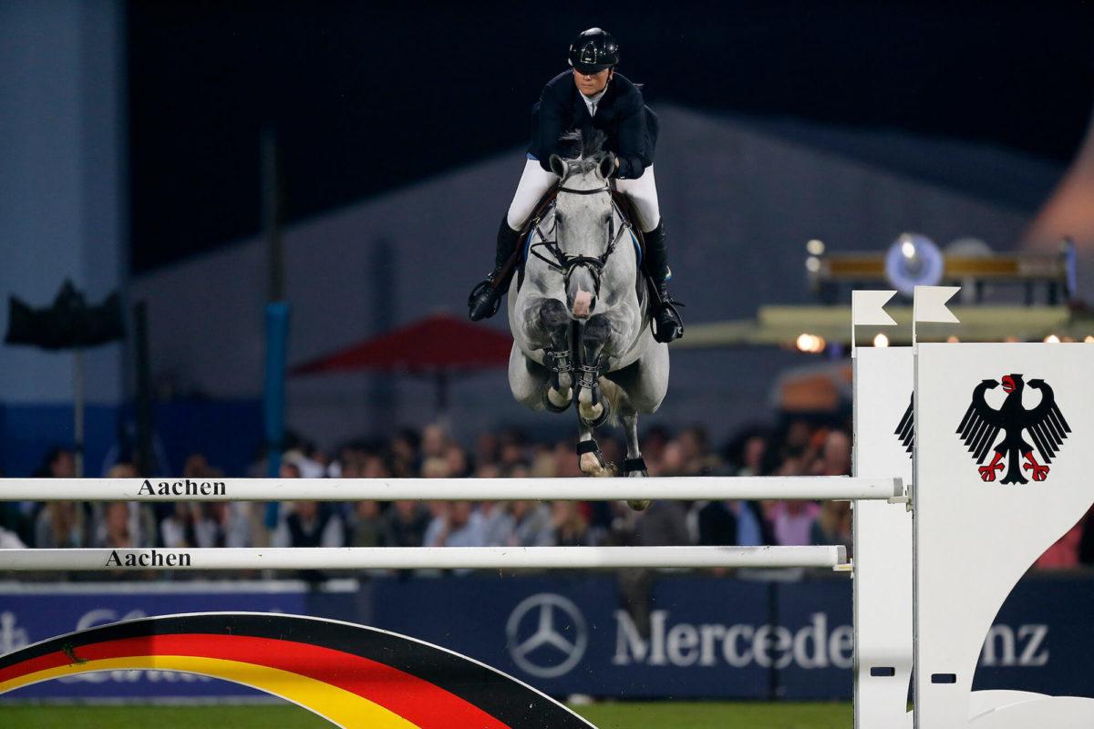 En häst och person fångade mitt i ett hopp på en tävling