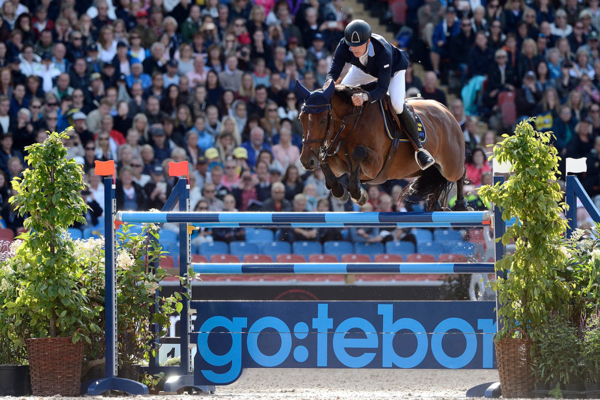 Ryttare och häst hoppar över hinder på en tävling