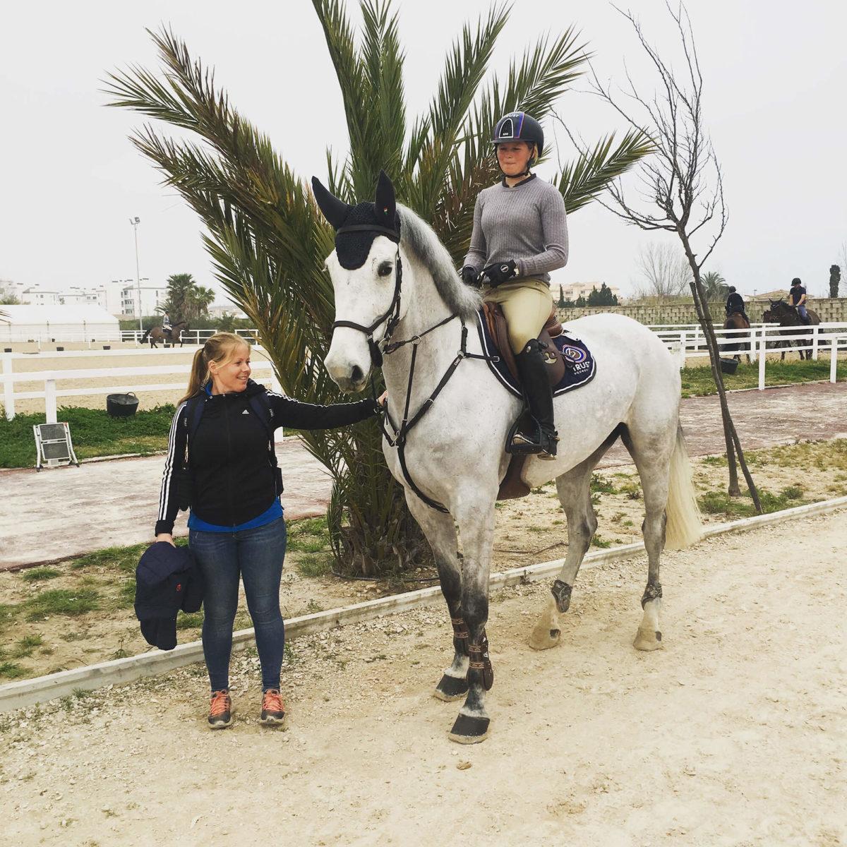 En person på en häst och till person fångas på bild framför en palm