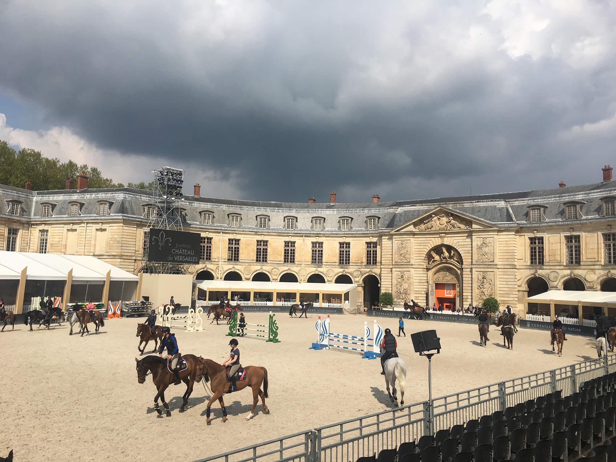 Många hästar och ryttare syns på bild med ett stort mörkt moln ovanför
