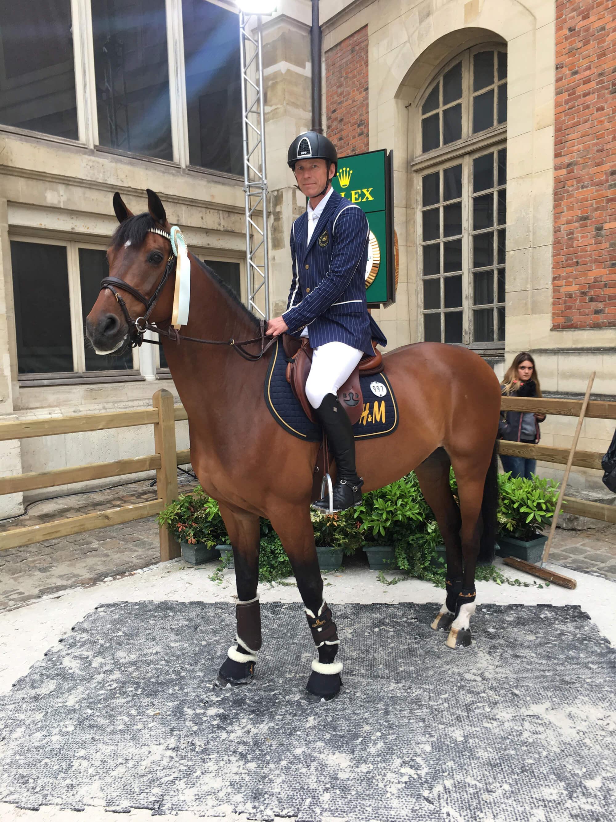 Ryttare och häst poserar utanför en byggnad