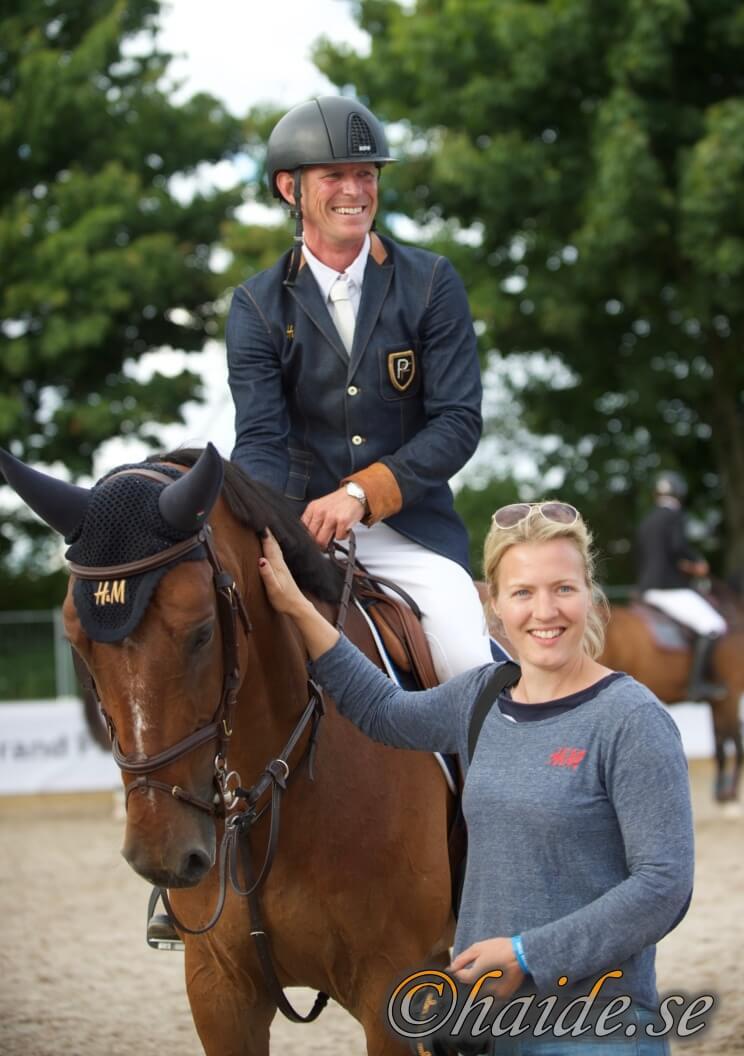 Peder på hästen med en tjej på marken som klappar hästen
