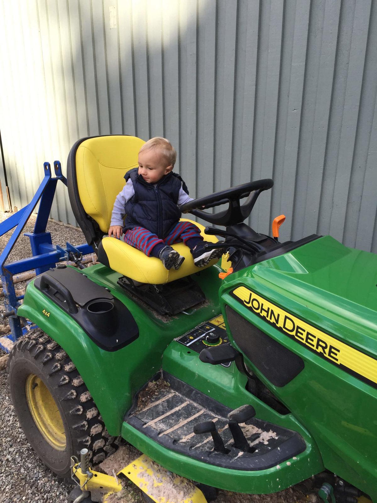 Litet barn sitter på en liten traktor