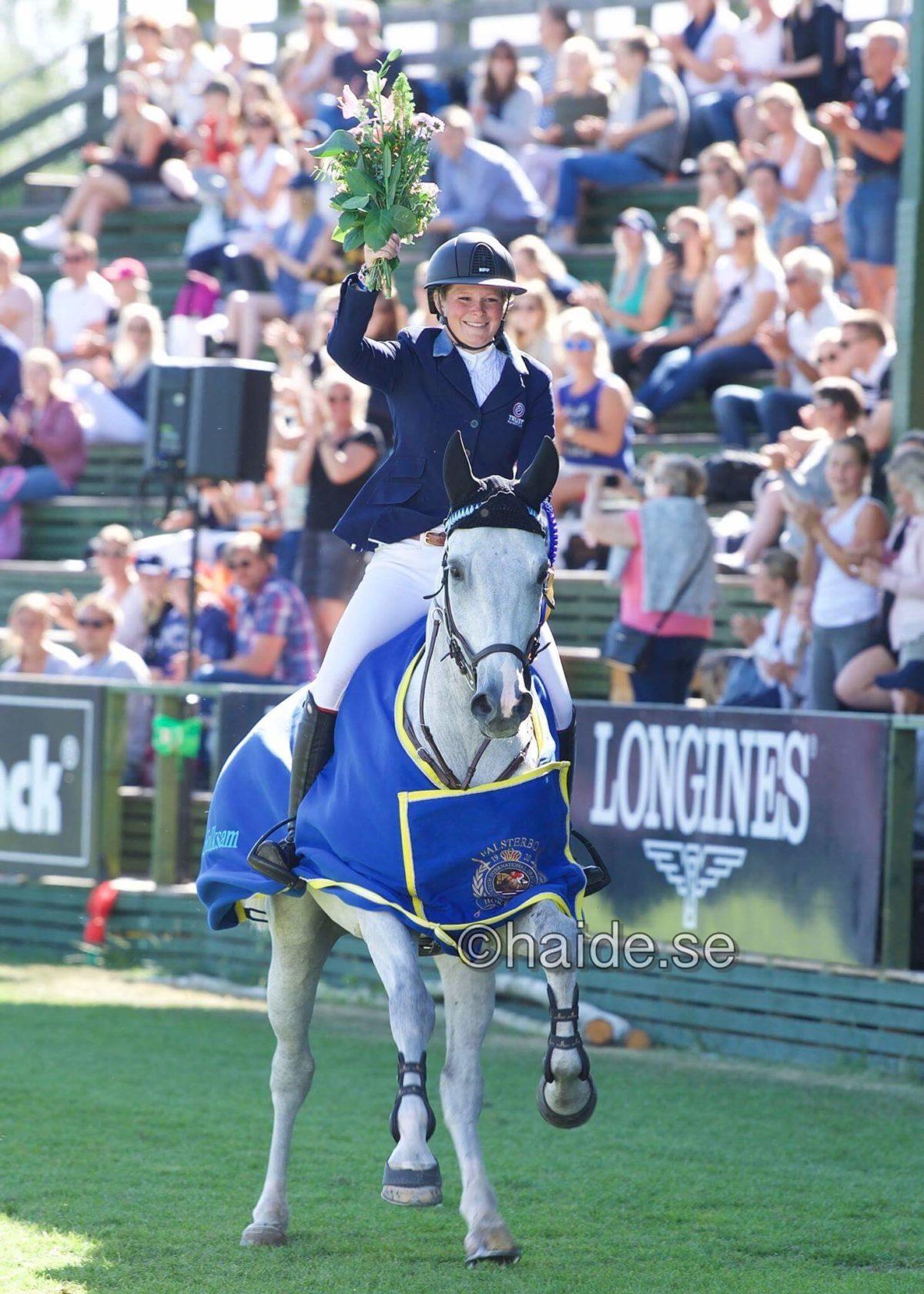Ryttare på en häst sträcker upp en blombukett i luften på en tävling