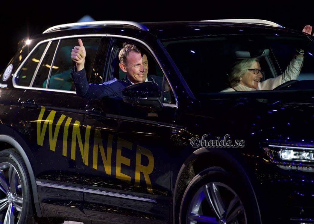 """Peder och en dam vinkar från en bil med texten """"winner"""""""