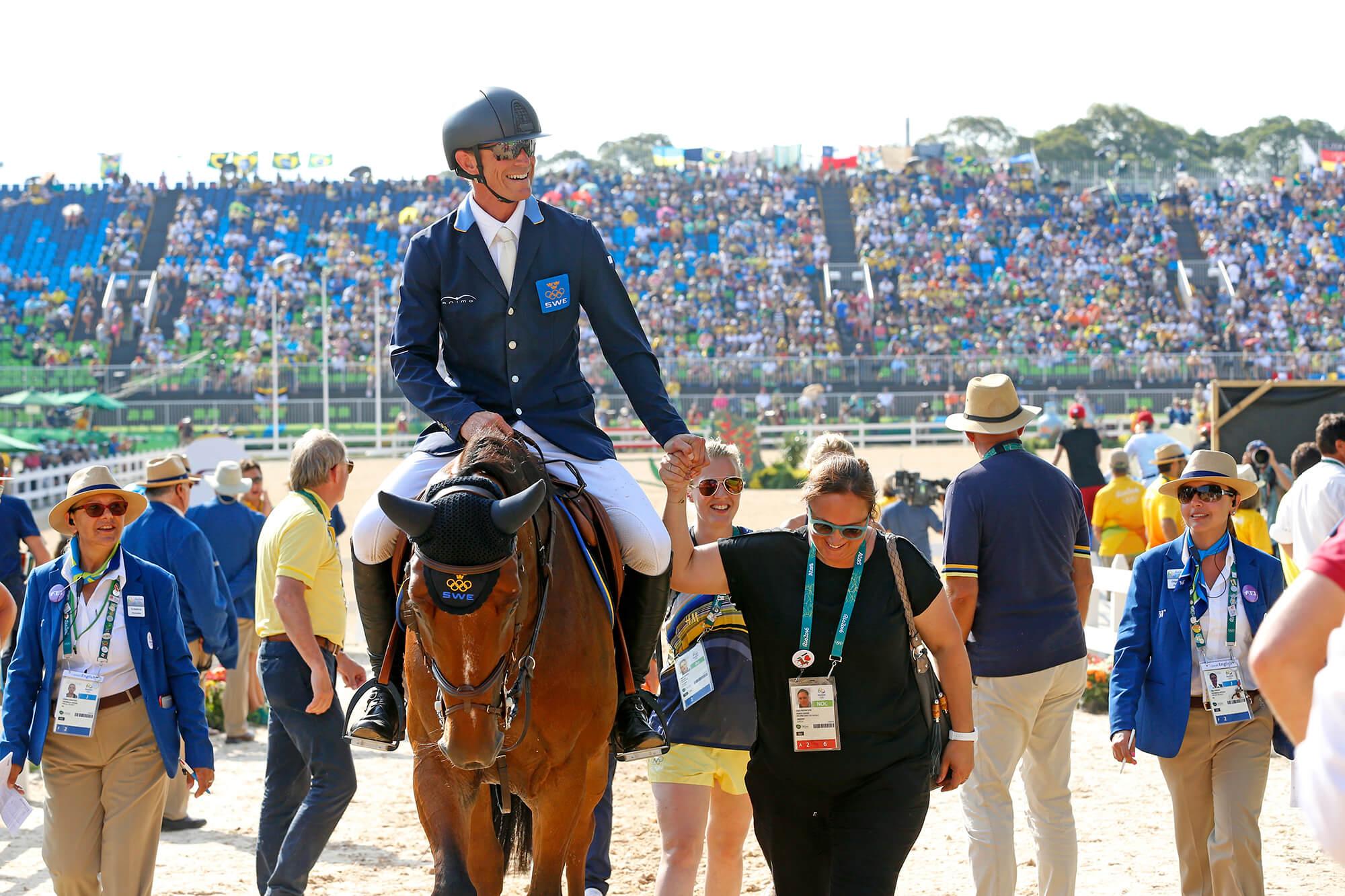 Peder på hästen med många personer runt om och publiken i bakgrunden vid OS