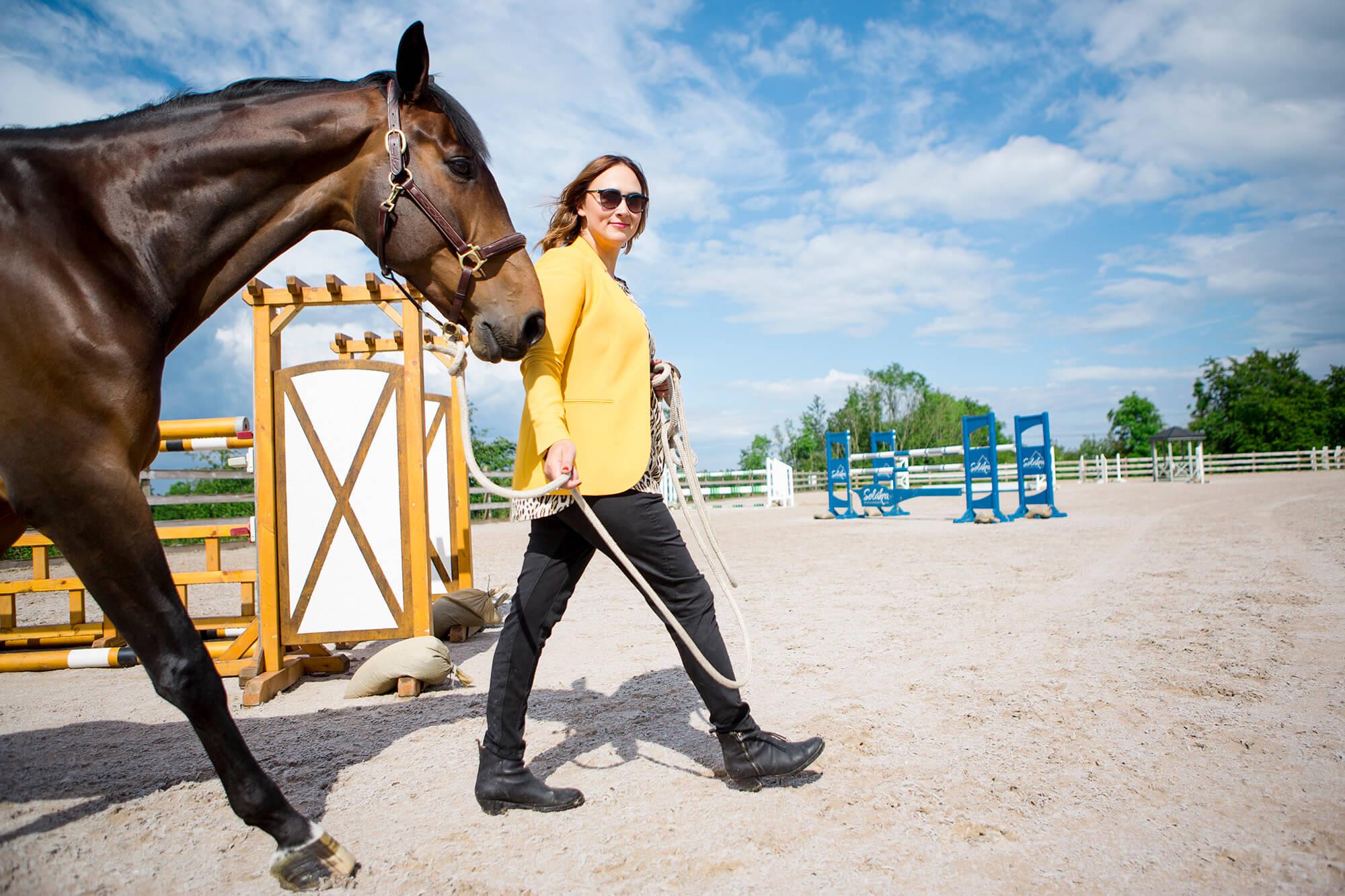 Fotografering av Lisen Fredricson och en häst med hinder i bakgrunden