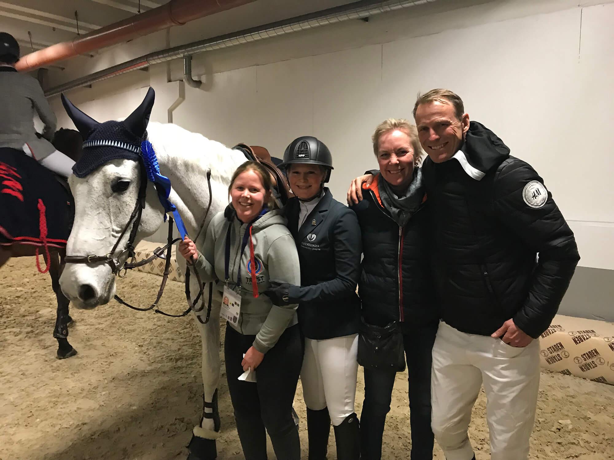 Peder och tre andra personer poserar med en häst