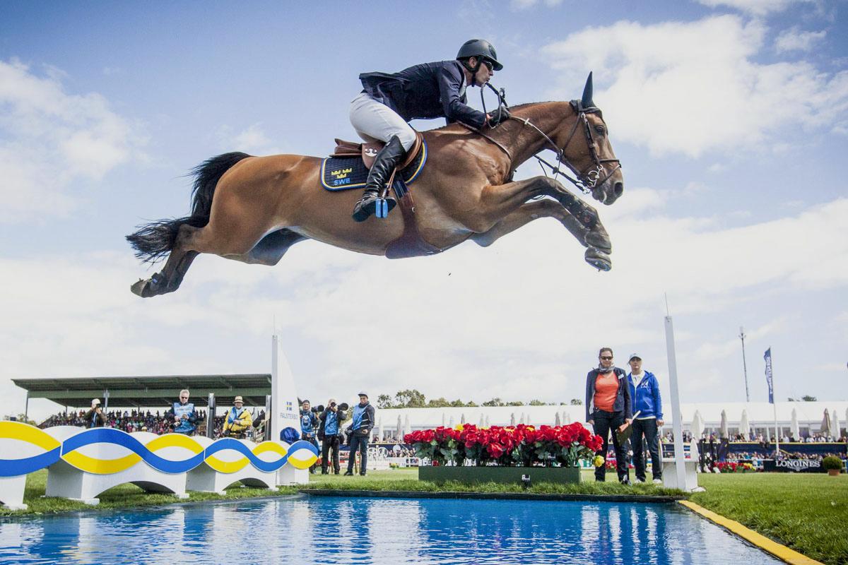 Ryttare och häst hoppar över ett vattenhinder på en tävling
